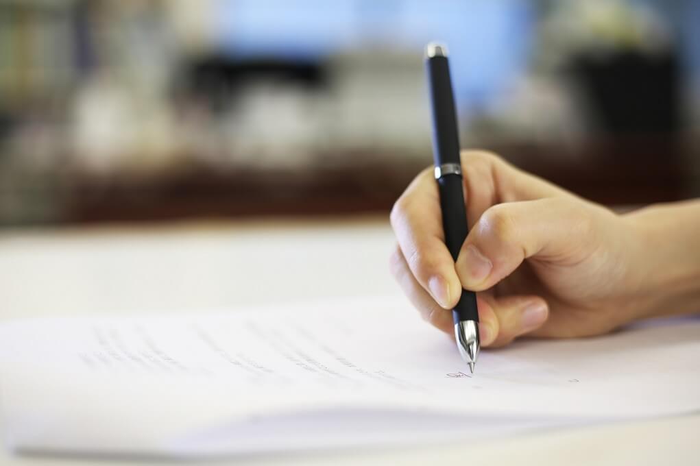 書類記入する人の手